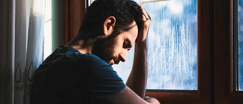 A man leans on a windowsill, head in hands