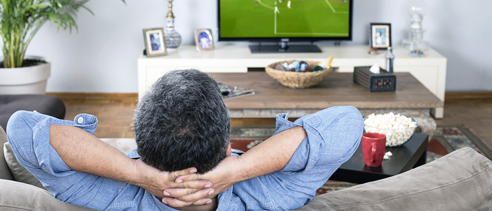 A man reclines on a sofa watching football on TV