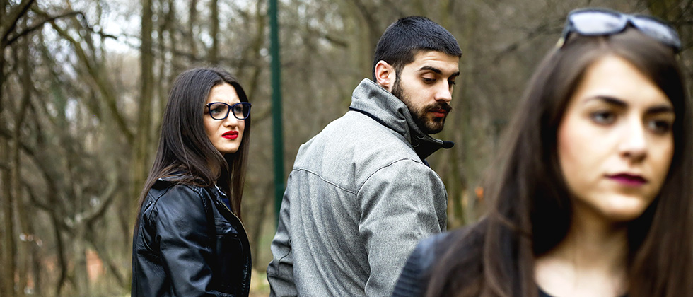 A man walks with his girlfriend while looking back at another woman