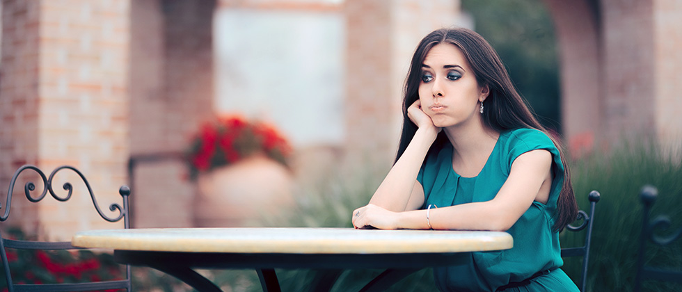 A woman sits on her own at a restaurant table, looking exasperated