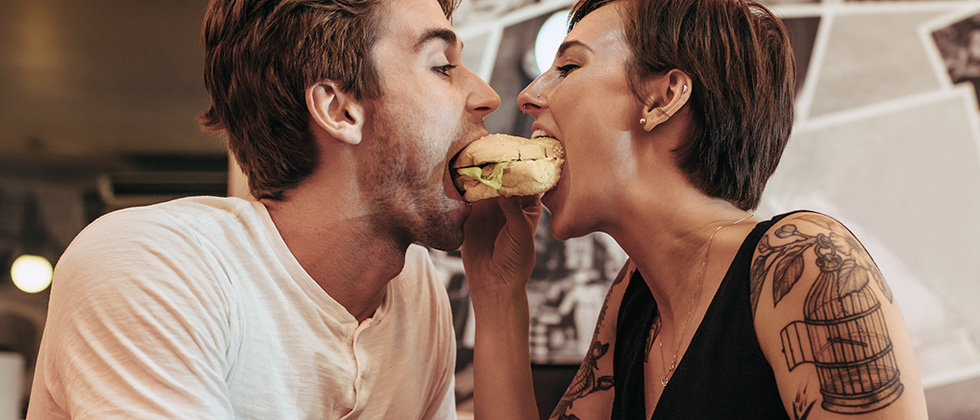 A young couple share a burger in a restaurant