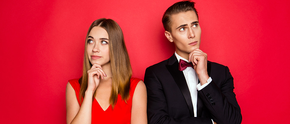 A woman in a red dress and a man in a dinner suit stand shoulder-to-shoulder, but look away from each other