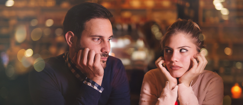 A couple in a cafe looking seriously at each other