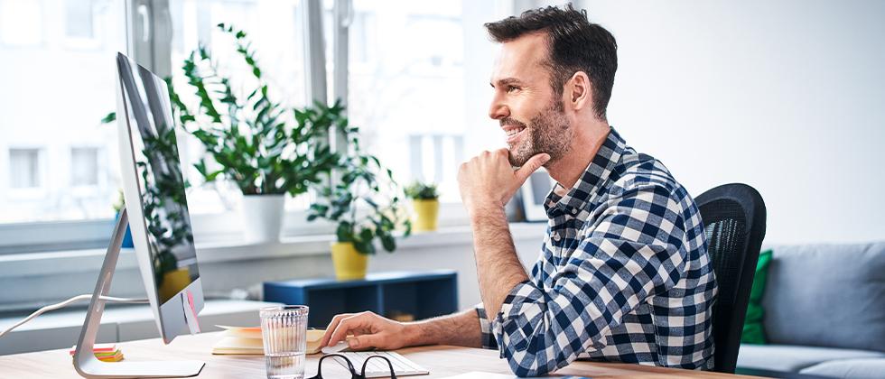 A man sits at his desk, looking at his monitor