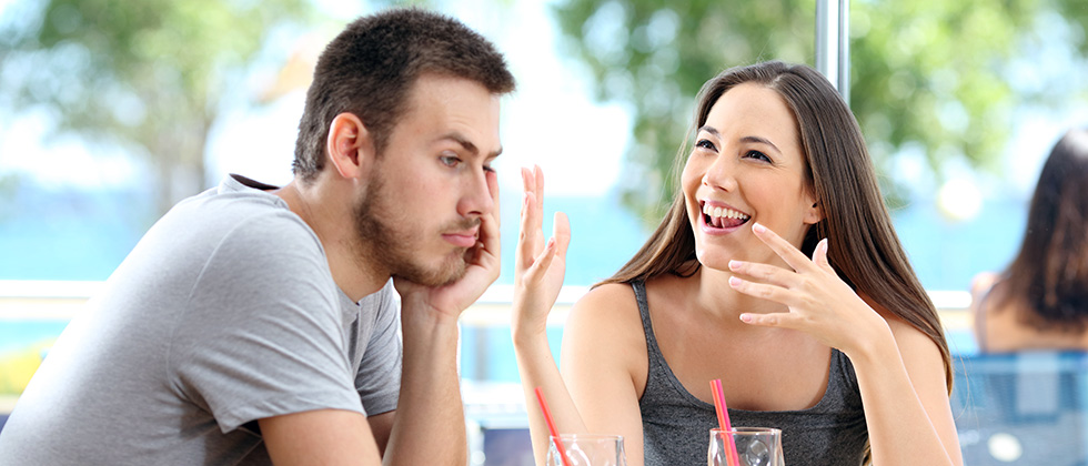 A man looks bored in a restaurant while his partner talks on obliviously