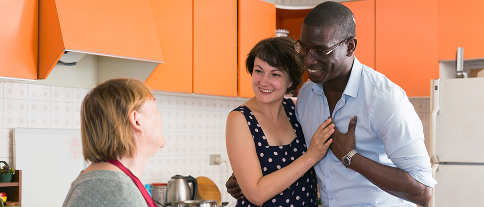 A man and his partner speak to her mother in a kitchen