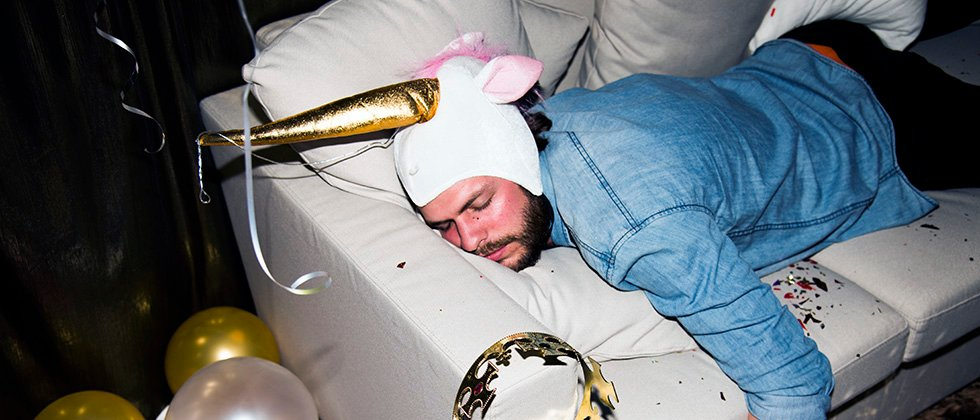 Drunk man passed out on a sofa at a party