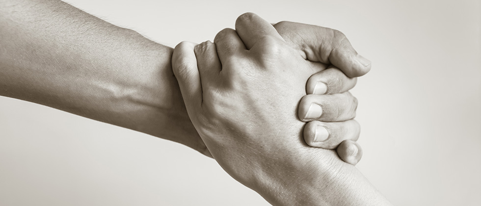 Close-up of a man and woman's hands clasped together