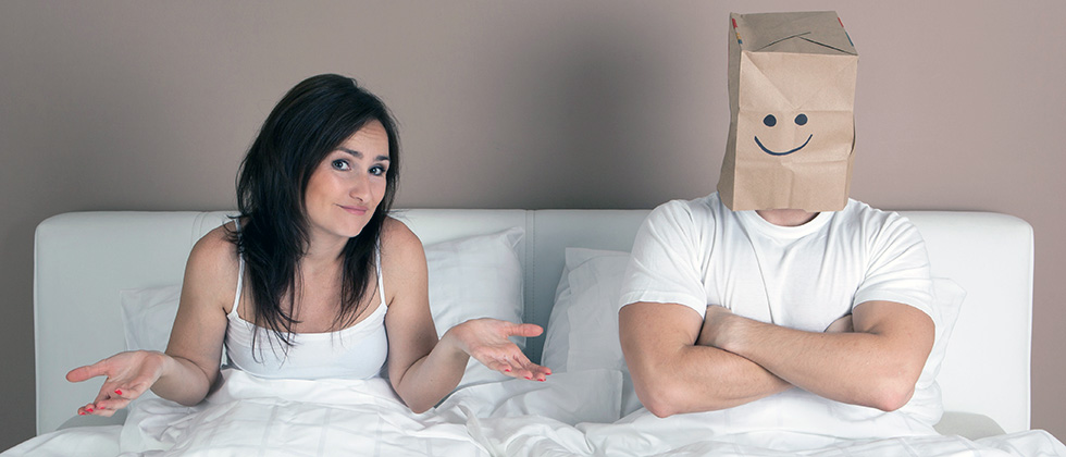 A couple in bed, the woman shrugs her shoulders, the man wears a paper bag over his head