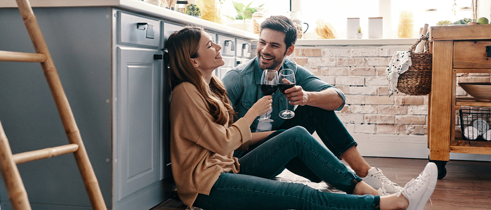 A coupld drinking wine while sitting on the floor of their kitchen