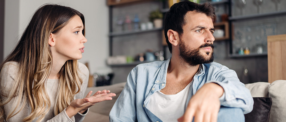 A couple sit on a sofa, the woman making a pleading gesture towards the man as he looks away