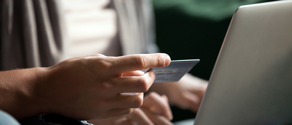 Close-up of a man's hands holding a credit card in front of a laptop