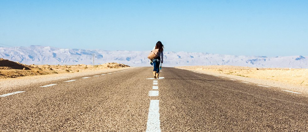 A woman walks away down an empty road in a desert with mountains on the horizon