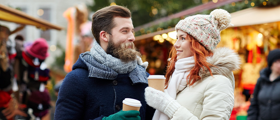 A couple dressed for cold weather smile at each other in the winter market
