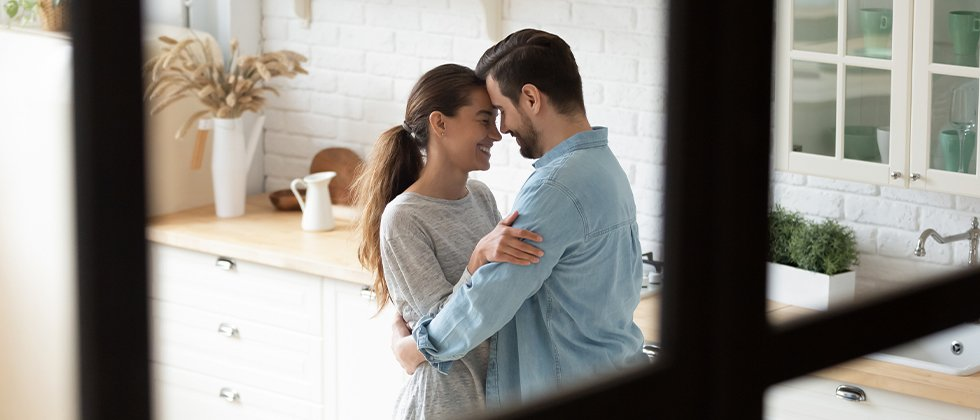 A couple dancing in a kitchen and smiling at each other