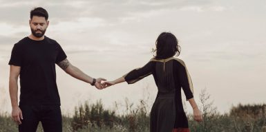 Couple in a field holding hands but walking away from each other