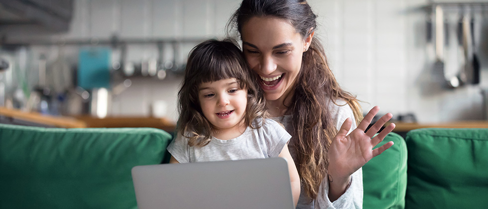 A young girl sits on her mother's lap as they both look at a laptop screen