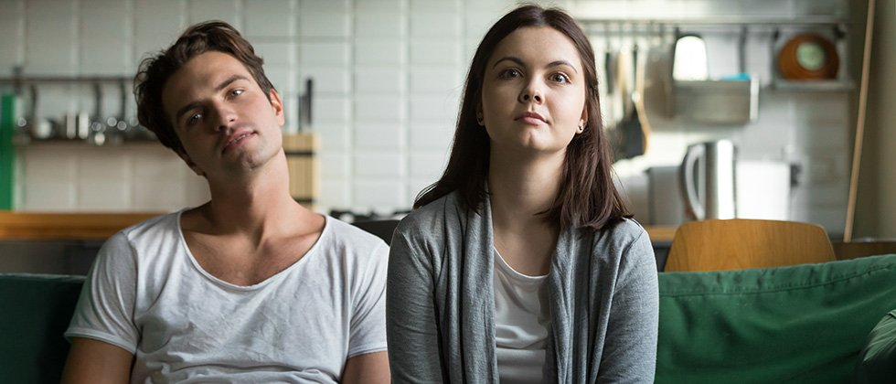 Bored-looking couple sit together on a sofa, staring forward vacantly