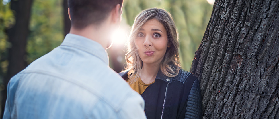 A woman looks over her partner's shoulder with an uncertain expression