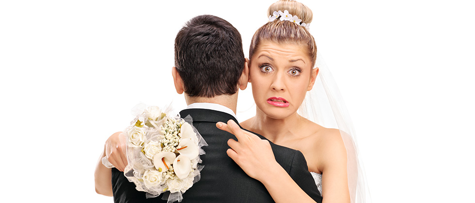 A bride hugs her new husband with fingers crosssed behind his back
