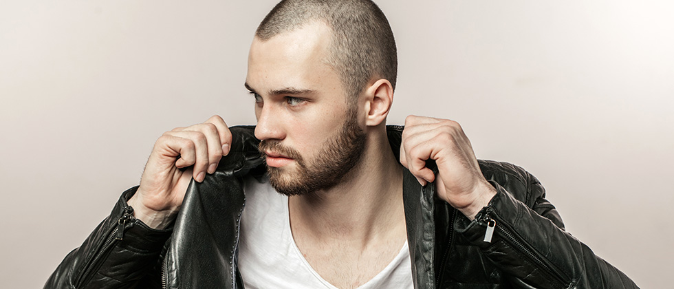 A young, shaven-headed man pulls the collar up on a black leather jacket