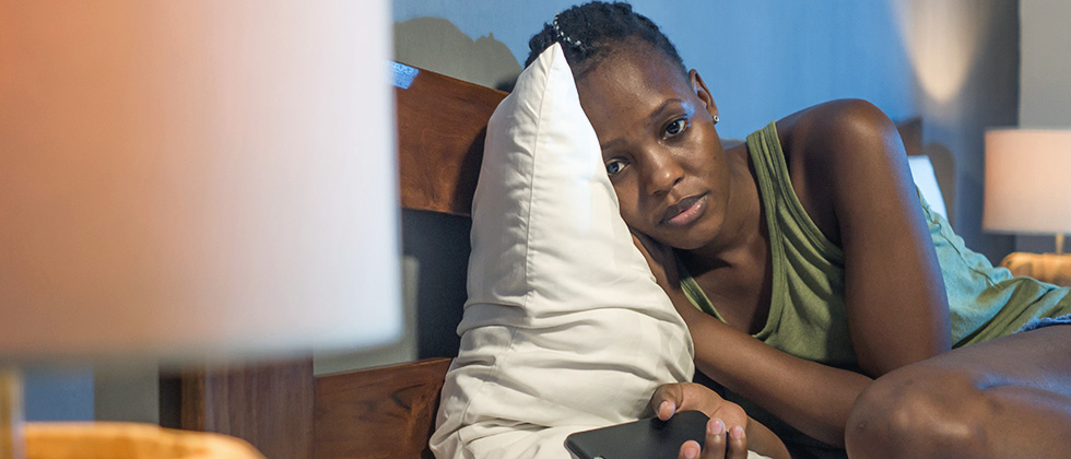 A sad-looking young woman lies curled up in bed, holding a phone