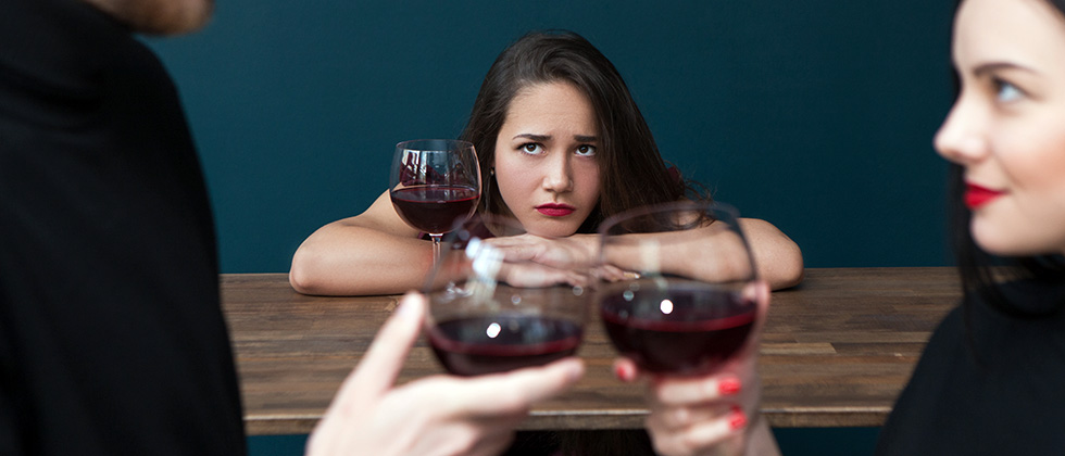 A woman in a wine bar looks troubled as she looks at two of her friends talking