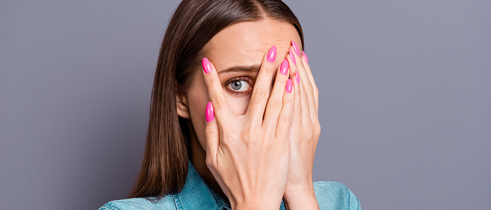A woman looks through her fingers in embarrassment