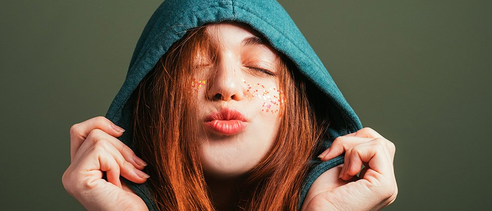A red-haired young woman in a hood purses her lips