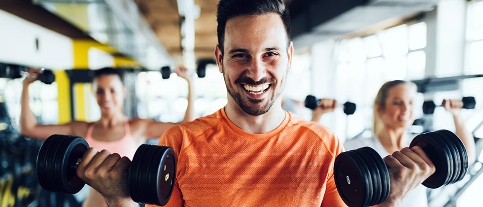 A man in a gym looks to camera while holding a dumbbell weight in each hand