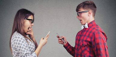 A couple face each other, looking surprised while staring at their phones