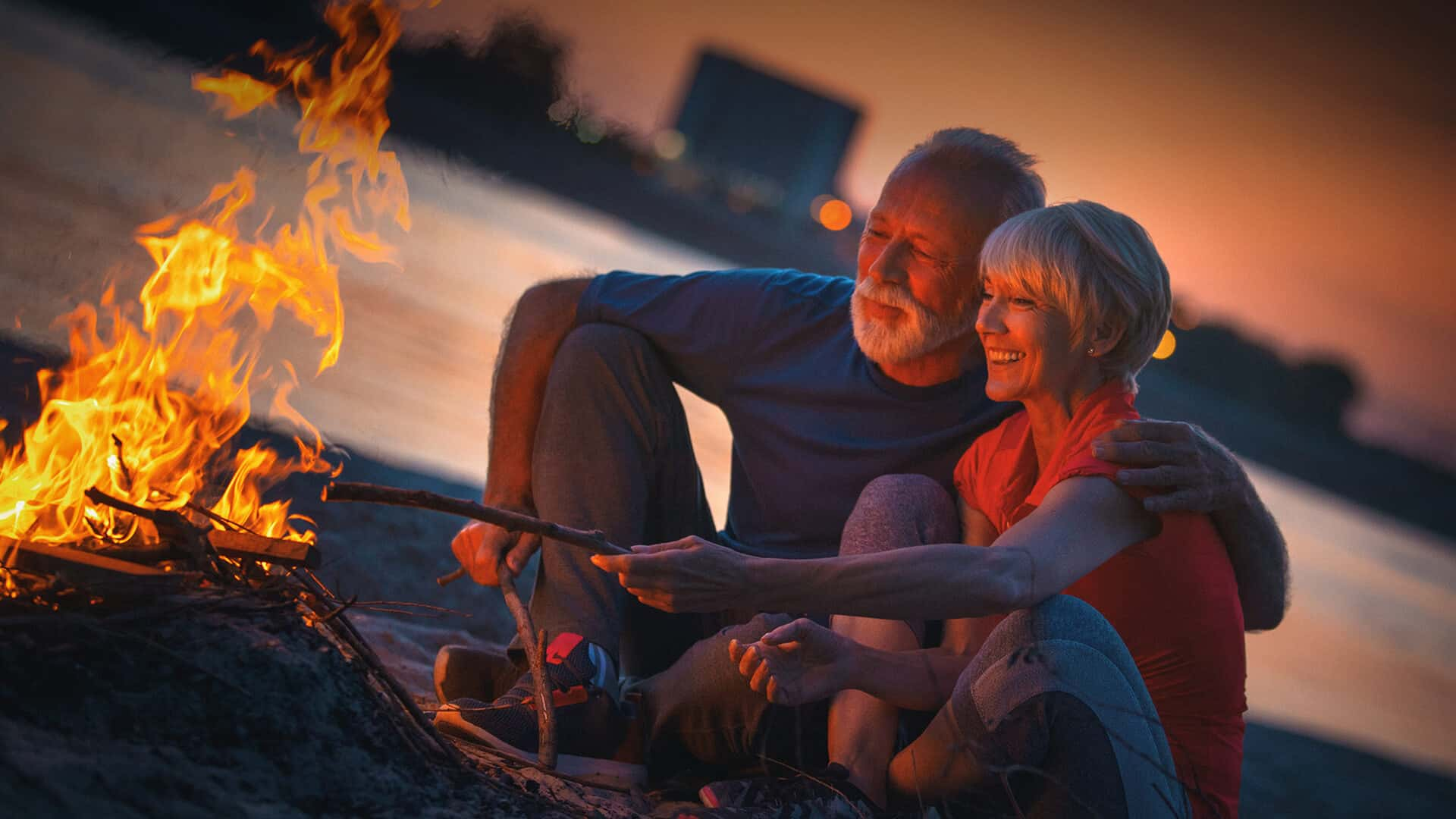 60s dating symbolized by a happy couple sitting in front of a campfire in UK