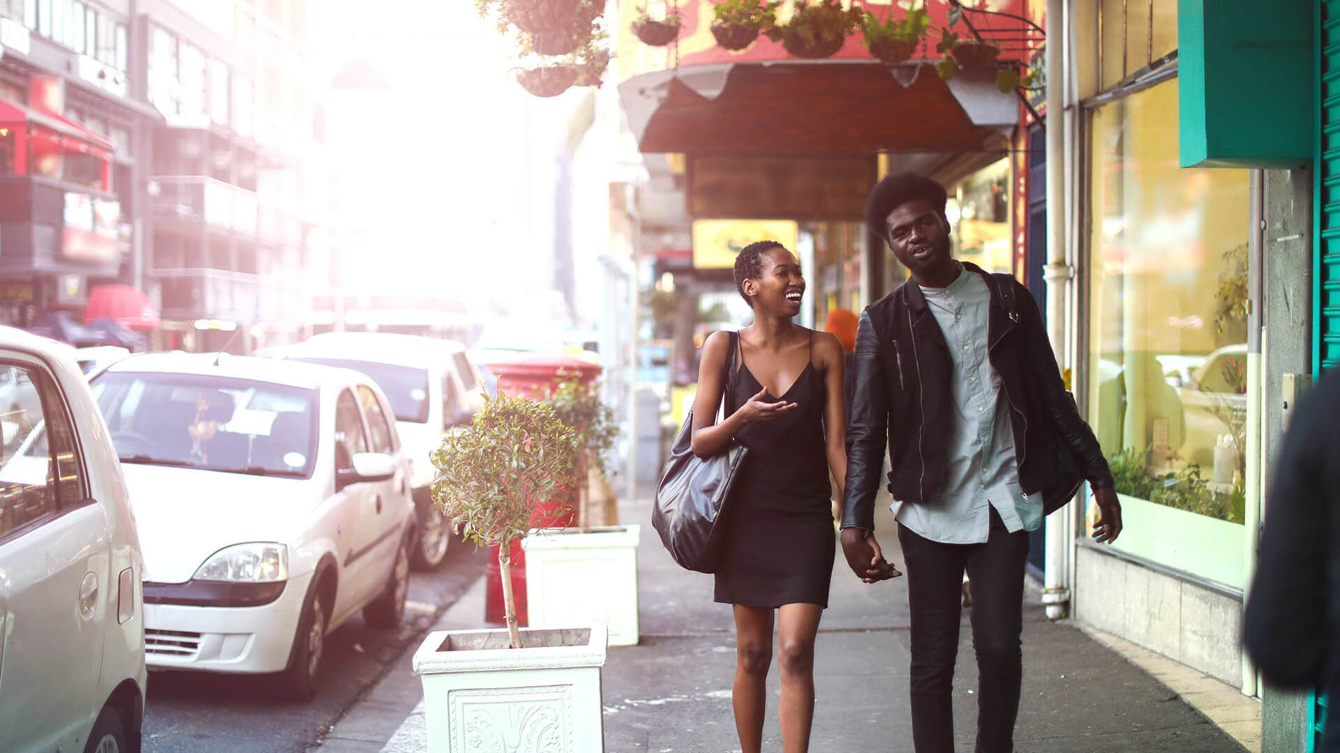 African dating symbolized by a man and woman strolling hand in hand through the city on their first date