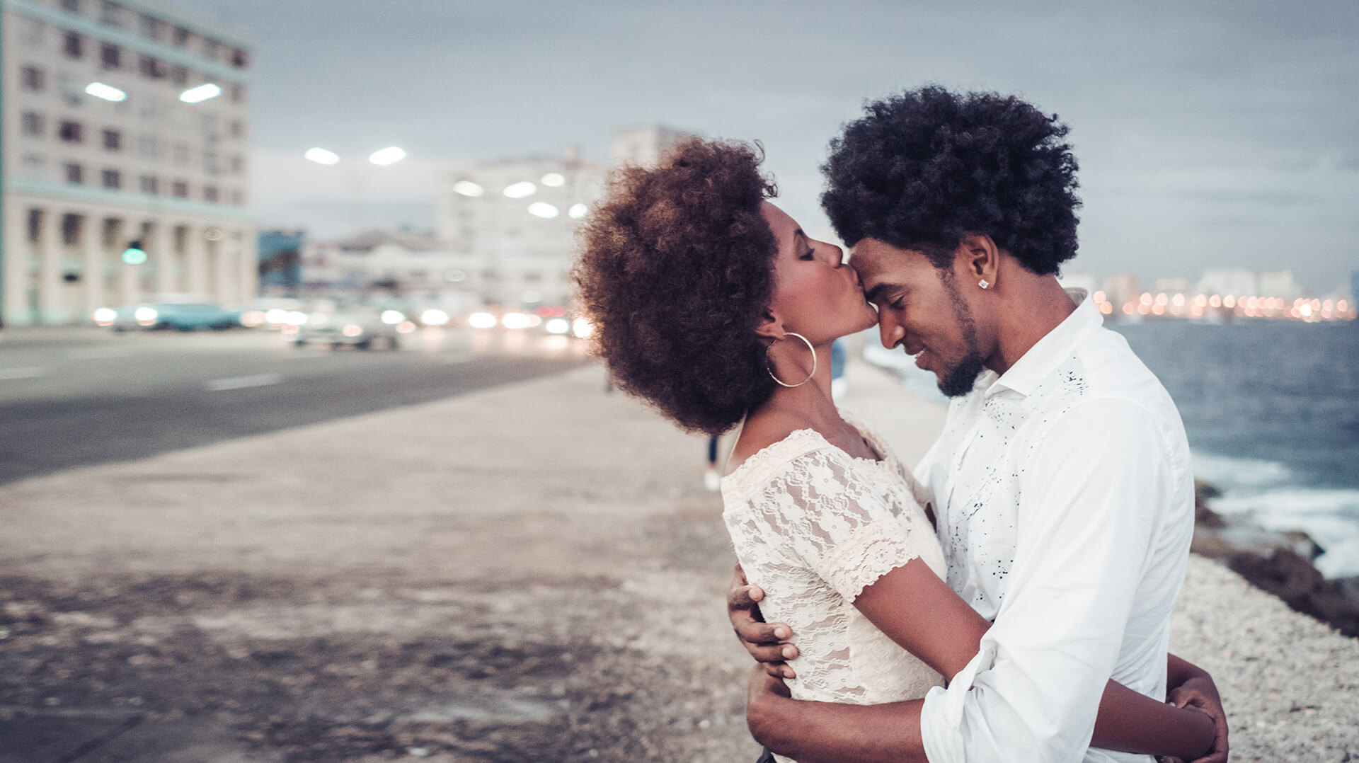 carribean dating symbolized by a woman who embraces a man and gives him a kiss on the forehead at the beach