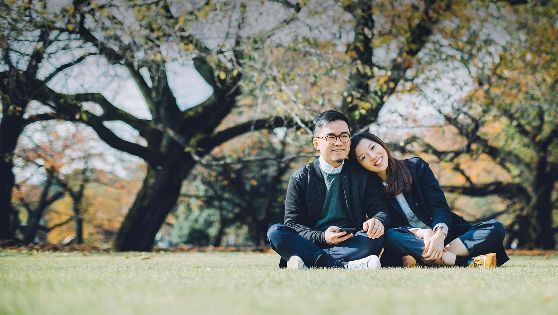 Japanese dating symbolized by a man and woman sitting cross-legged next to each other on a green field in UK
