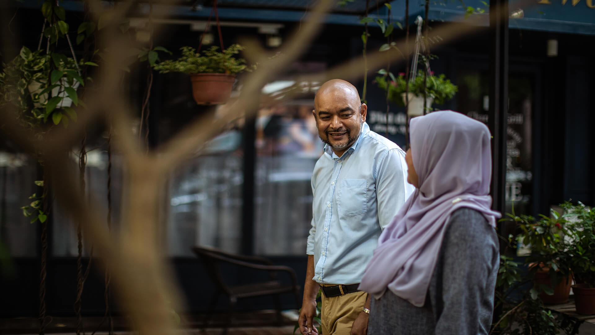 Muslim Dating symbolized by a muslim man and woman strolling through a park in UK