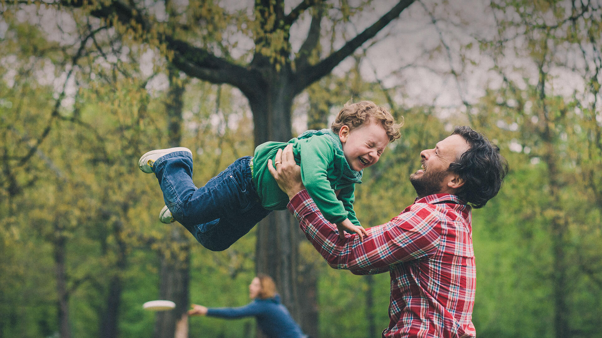 Single parent dating symbolized by a single dad who is tossing his little son in the air on a playground in UK