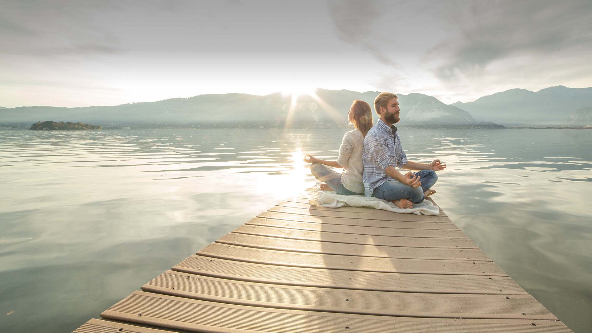 Spiritual dating symbolized by a couple meditating together on a dock