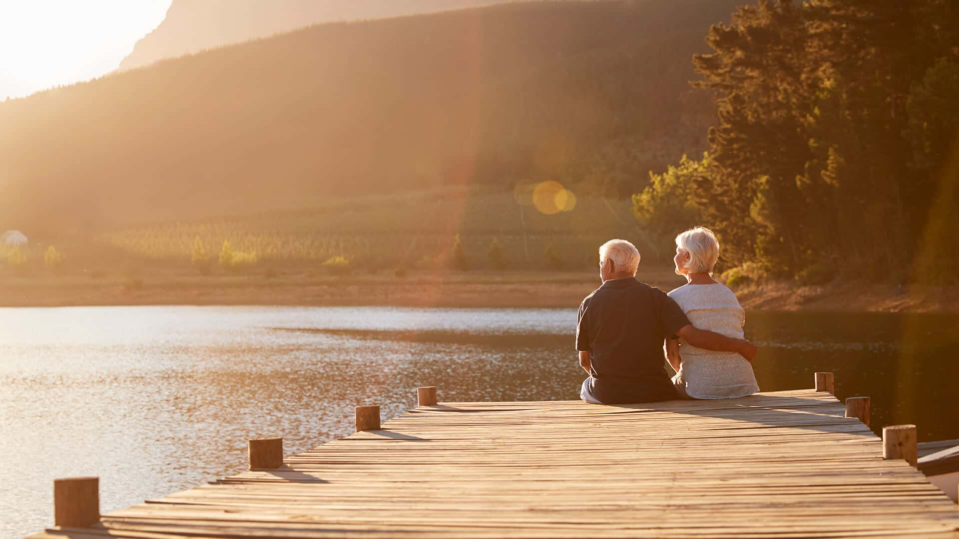 Widowed dating symbolized by a man and woman sitting next to each other on a dock end enjoy the sundowner