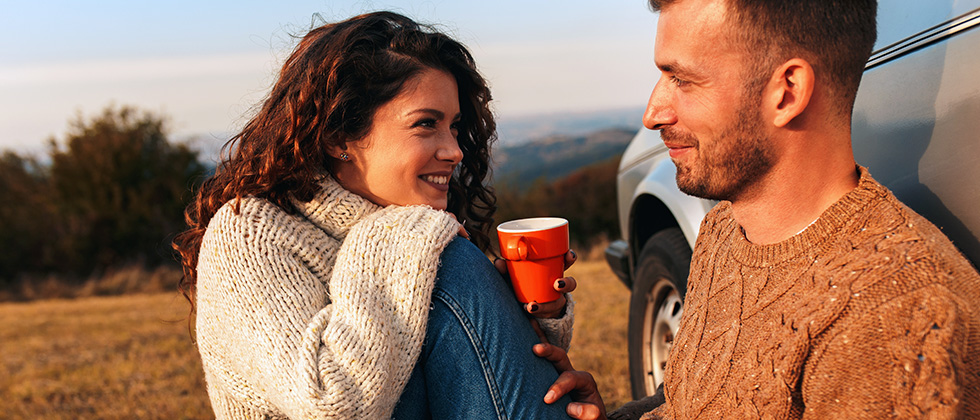 A young couple enjoy a picnic in a field, sitting in front of a car