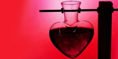 A heart-shaped test tube in a stand against a red background