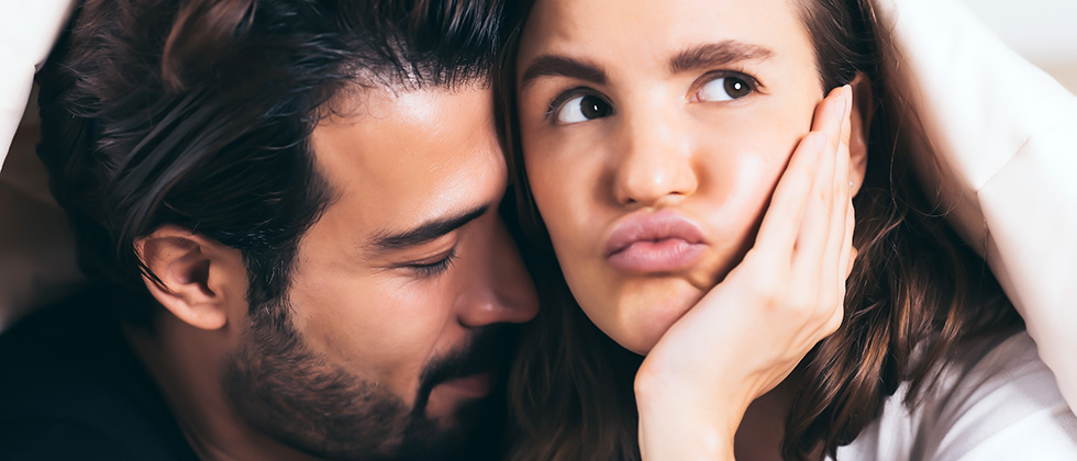 A woman looks bored while her male partner nuzzles her neck