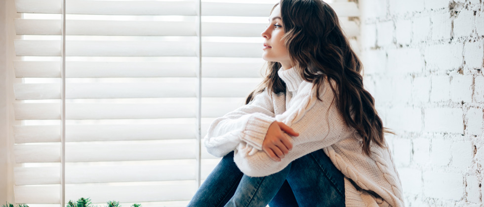 Woman looks out the window and thinks about how to get over ex