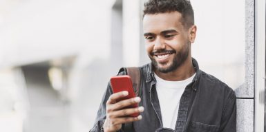 Young man leaning against a wall and smiling at his phone