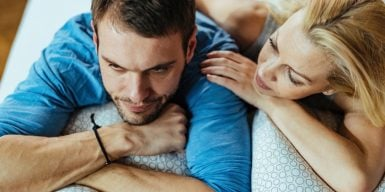 Woman hugs man on sofa - she loves him too much
